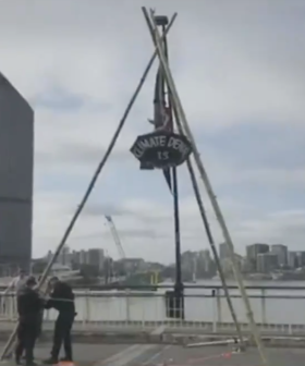 Aussie Protester With Umbrella Hangs From Bridge On Tripod